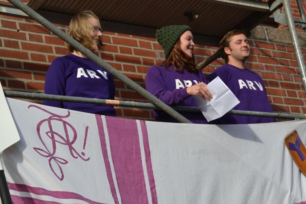 Eine Person aus einer Gruppe von drei Personen, die auf einem Baugerüst stehen. hält eine Rede, vor ihnen hängt eine Vereinsflagge