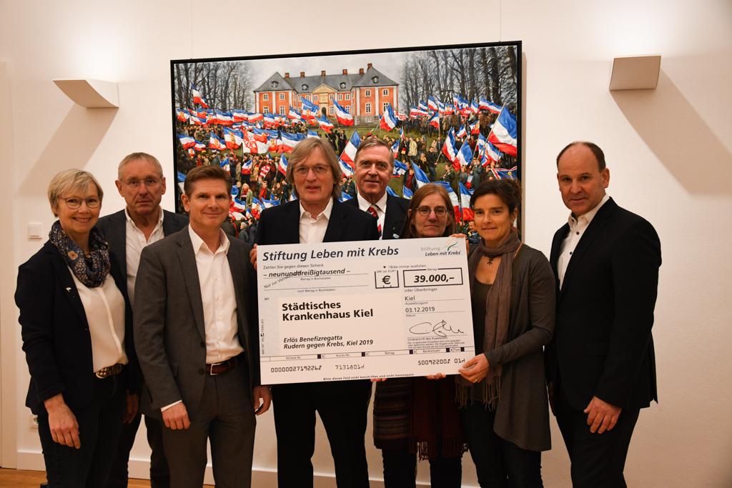 Gruppenbild mit acht Personen, die einen großen Spendenscheck vor einem Gemälde in den Händen halten
