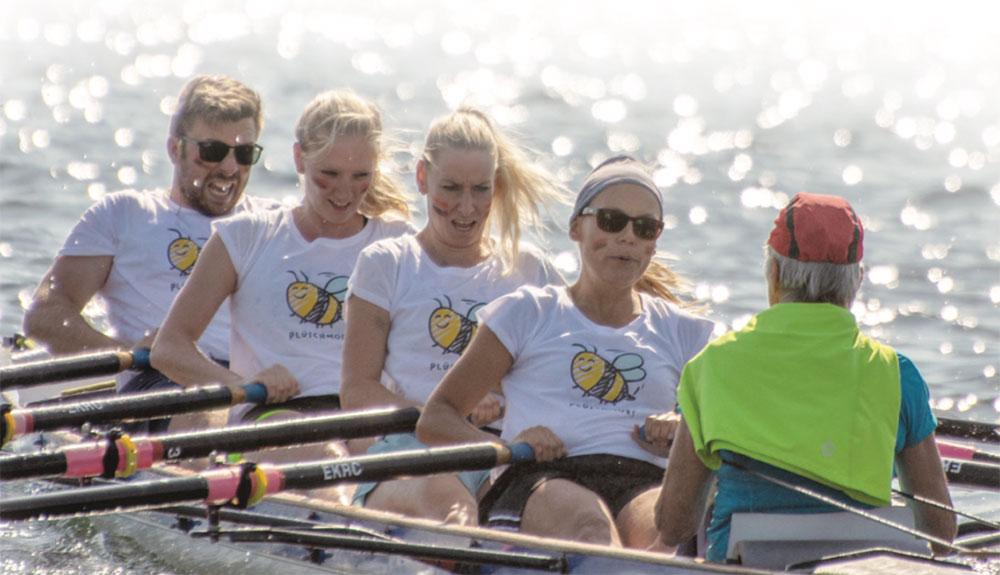 Vier Personen hintereinander in einem Ruderboot mit Ruderskulls in den Händen und vor ihnen sitzt eine Steuerfrau